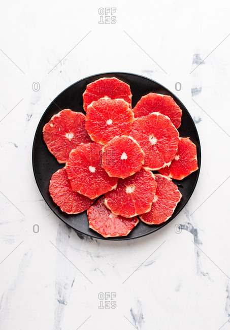 Overhead view of black ceramic plate with sliced peeled grapefruit
