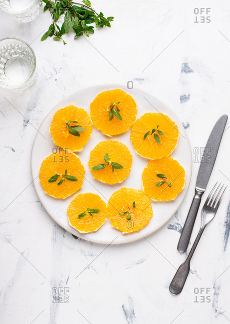 Overhead view of white ceramic plate with sliced peeled orange and glass of still water