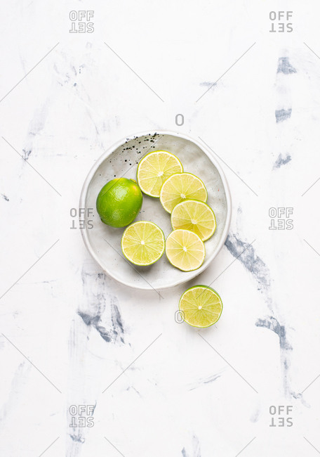 Overhead view of sliced lime on ceramic plate
