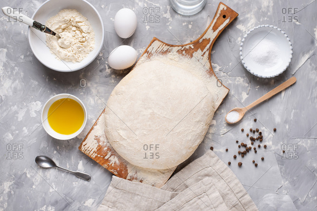 Overhead view of dough for pizza on wooden cutting board amidst ingredients, flour and eggs
