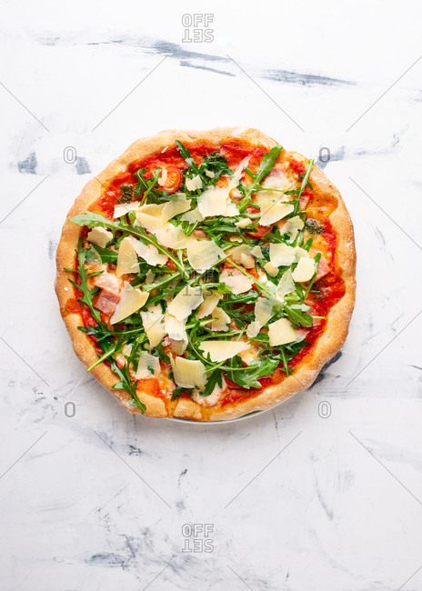 Overhead view of fresh whole pizza with cheese parmesan, arugula, tomatoes and ham served on ceramic plate
