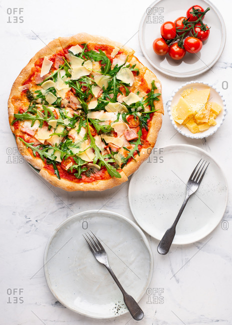 Overhead view of fresh sliced pizza with cheese parmesan, arugula, tomatoes and ham served on ceramic plate