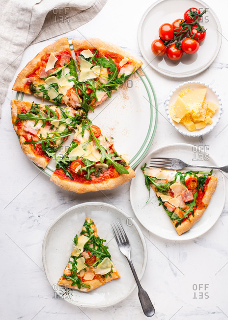 Overhead view of fresh sliced pizza with cheese parmesan, arugula, tomatoes and ham