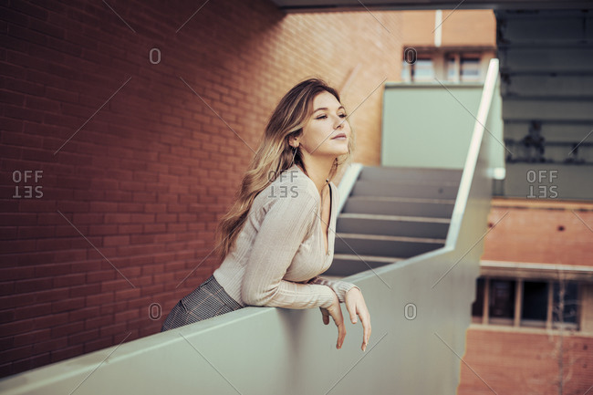 Pretty blonde girl leaning over ledge of a city building looking away