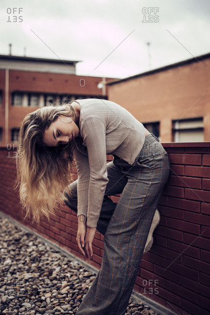 Blonde woman reaching down while leaning on a red brick wall
