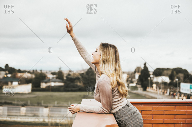 Young woman leaning on a brick wall and waving her hand