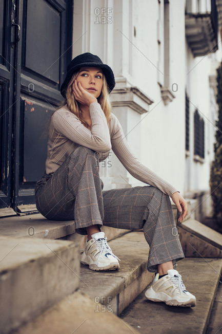 Pretty blonde woman sitting on building steps in the city