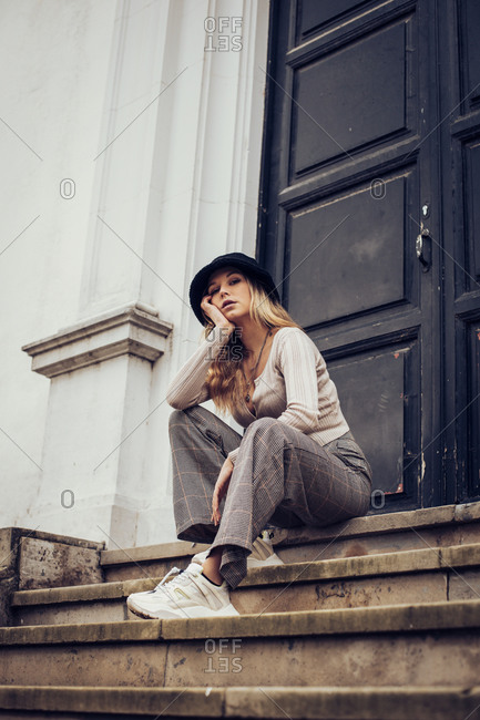 Young blonde woman sitting on building steps in the city