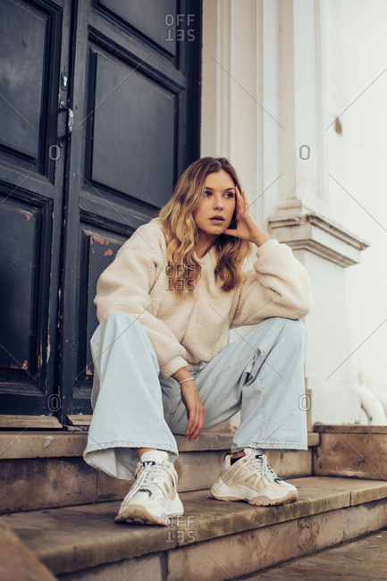 Urban portrait of a pretty blonde girl sitting on steps looking away