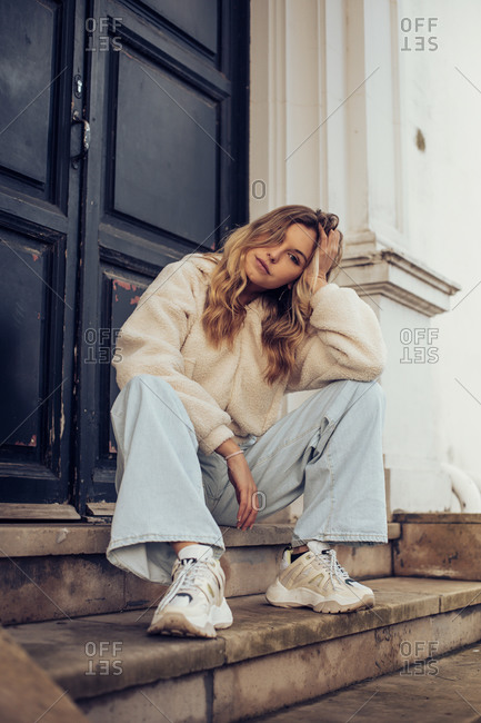 Pretty blonde girl sitting on steps on building in the city