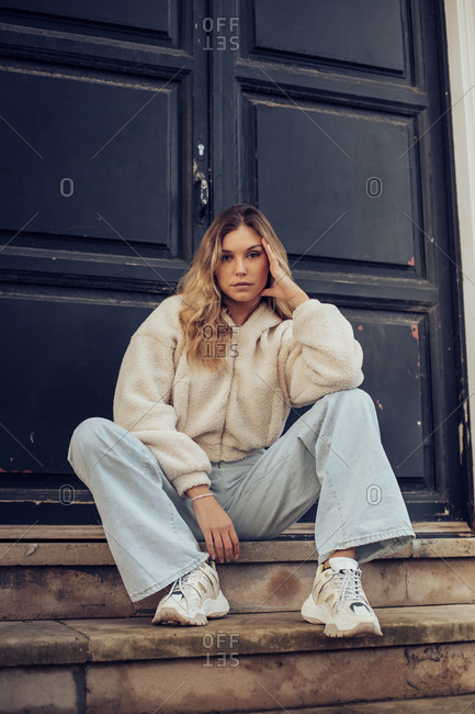 Young blonde girl sitting on steps on building in the city