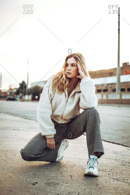 Urban portrait of a pretty blonde girl squatting near city street