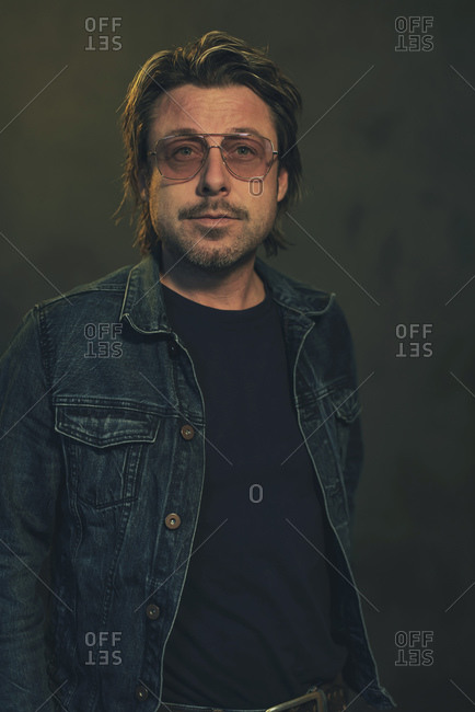 Man wearing a denim jacket and sunglasses