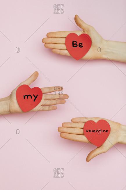 Three hands holding Valentine hearts