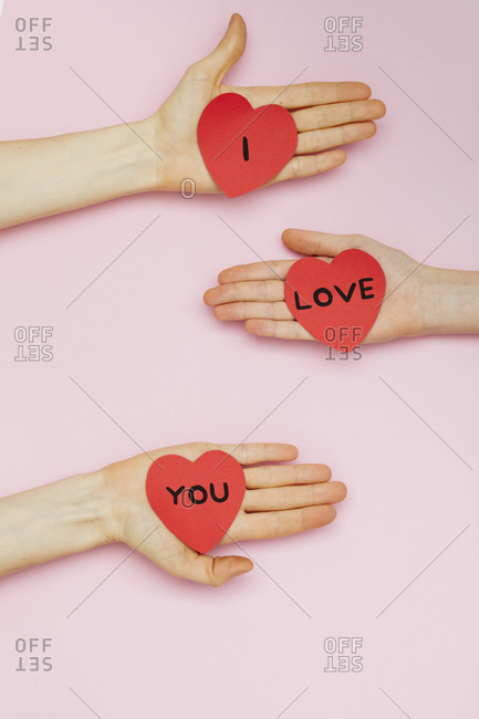 """Three hands holding Valentine hearts that read """"I love you"""""""