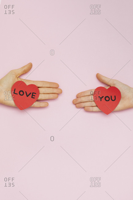 Two hands holding Valentine hearts that read \
