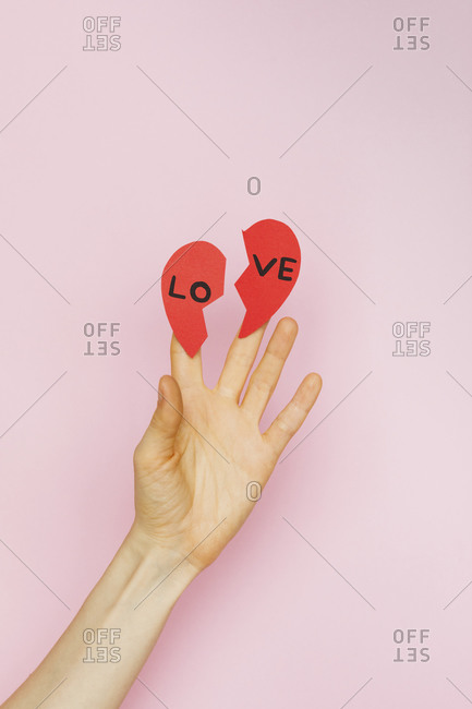 Hands holding two pieces of broken paper hearts