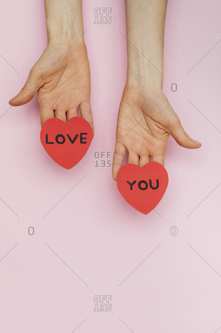 Hands holding Valentine hearts that read \