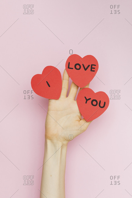 """A hand holding Valentine hearts that read """"I love you"""""""