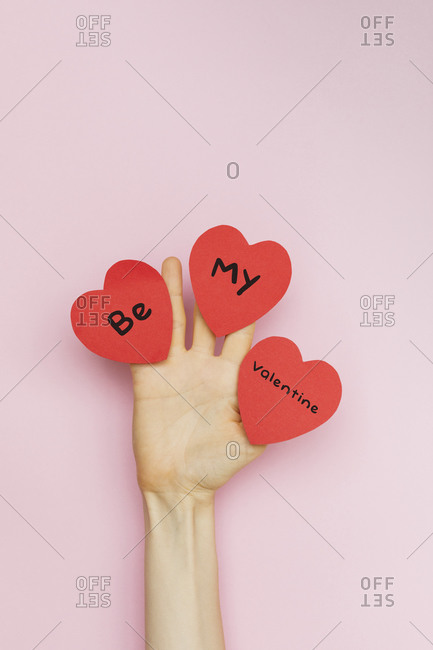 "A hand holding Valentine hearts that read ""Be my Valentine"""