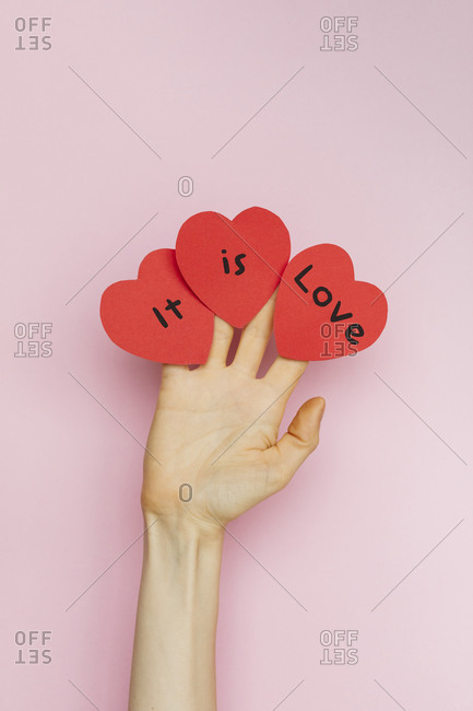 """A hand holding Valentine hearts that read """"It is love"""""""