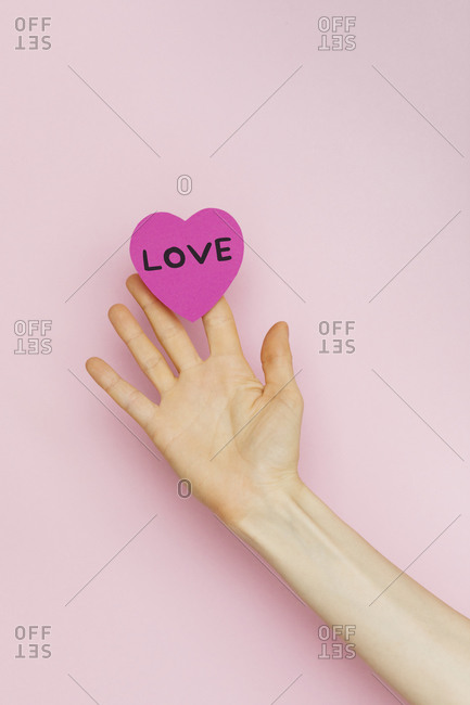 """Hands holding a Valentine heart that says """"Love"""""""