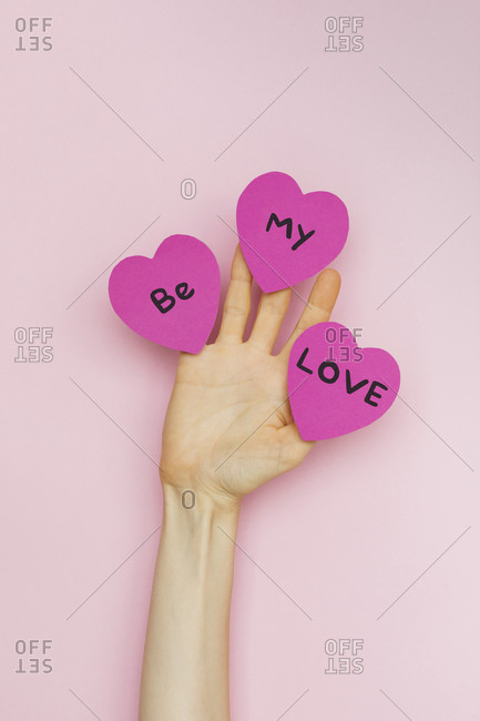 """A hand holding Valentine hearts that read """"Be my love"""""""