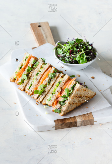Sandwich with salmon, cucumber and microgreens with whole-wheat bread, served on marble board
