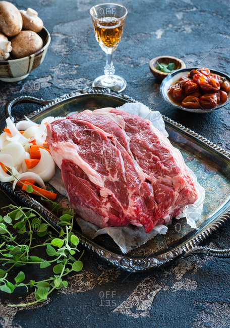 Raw fresh beef chuck steak roast on metal tray with knife and other ingredients for stew beside a glass of sherry wine