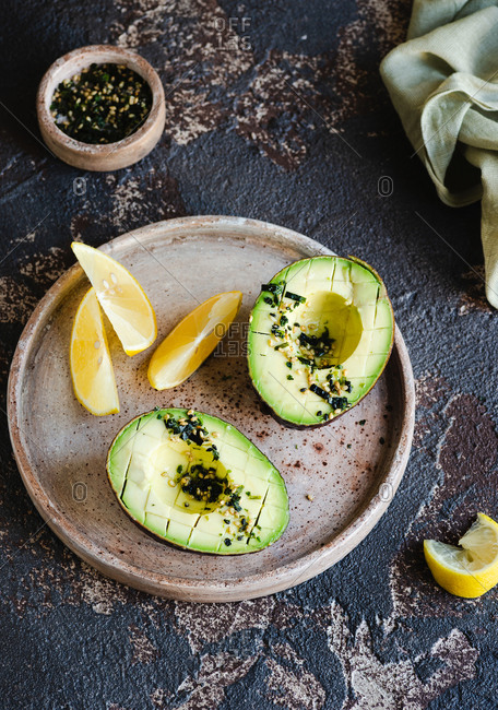 Halved avocado on plate with sesame seeds nori olive oil and lemon wedges