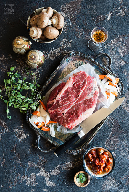 Overhead view of raw fresh beef chuck steak roast on metal tray with knife and other ingredients for stew beside a glass of sherry wine