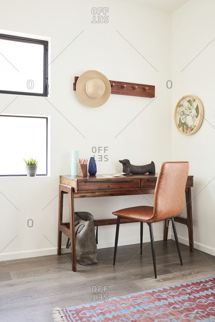 February 16, 2020: Simple wooden desk with brown leather chair