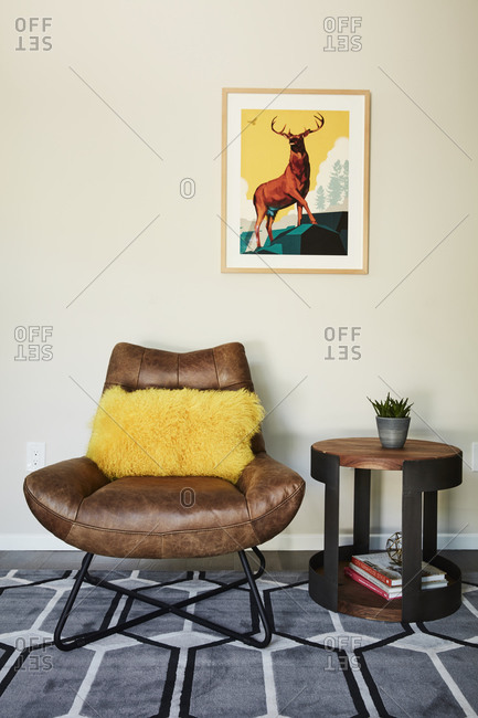 April 17, 2019: Brown leather chair with yellow pillow beside round side table