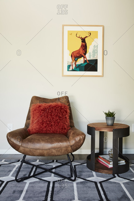 April 17, 2019: Brown leather chair with red pillow beside round side table