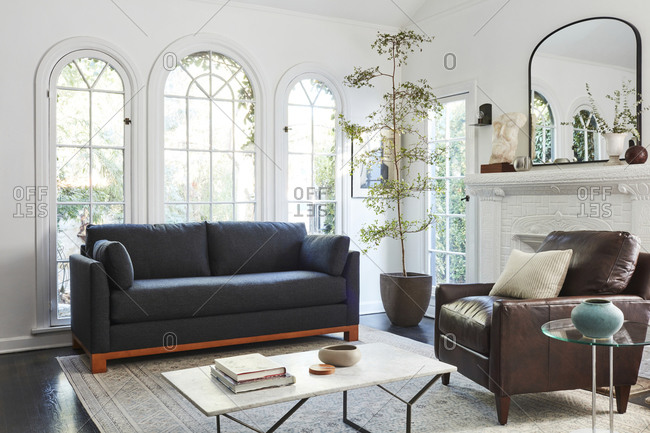 February 16, 2020: Interior shot of living room with tall arched windows and gray sofa