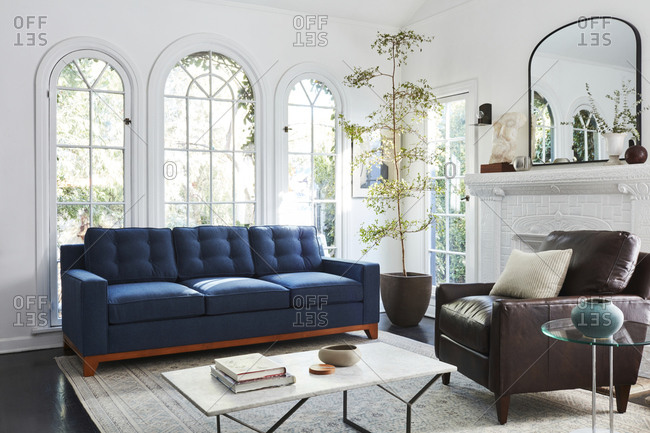 February 16, 2020: Interior shot of living room with tall arched windows and blue sofa