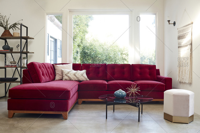 February 16, 2020: Living room with large red velvet sectional sofa