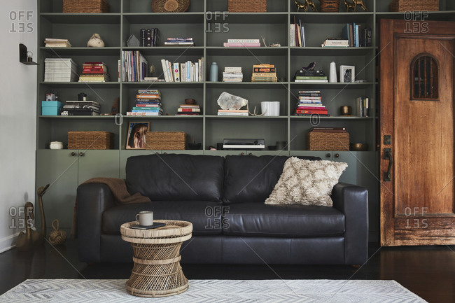 February 16, 2020: Black sofa in front of built in shelving unit in a home