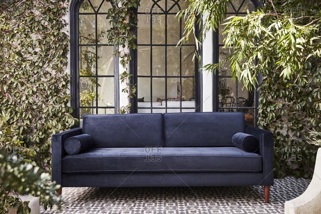 Blue velvet sofa on tile patio in front of large windows