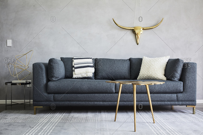 April 16, 2019: Simple gray living room with gold accents