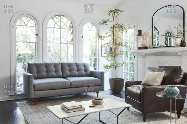 February 16, 2020: Interior shot of living room with tall arched windows and gray couch with leather chair