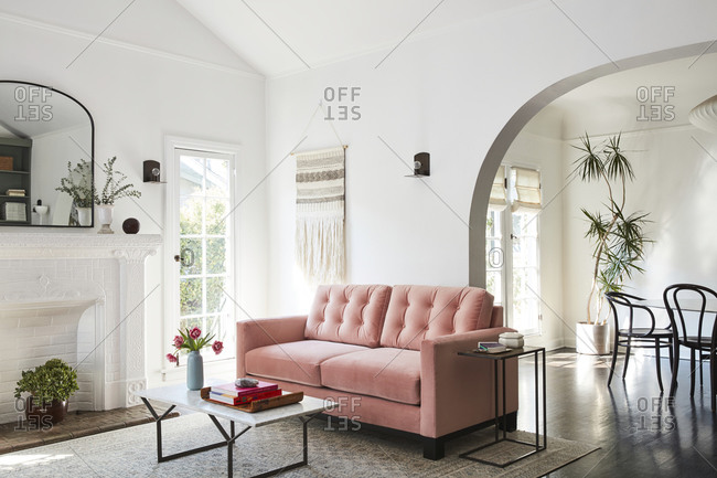 February 16, 2020: Pink loveseat sofa in a living room with arched doorway