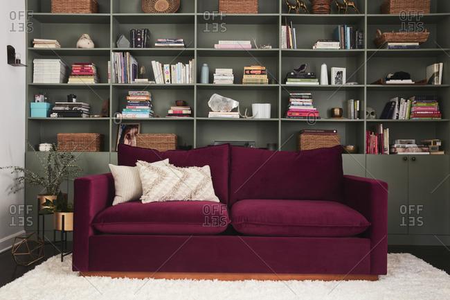 February 16, 2020: Velvet maroon sofa in front of large built-in shelving unit