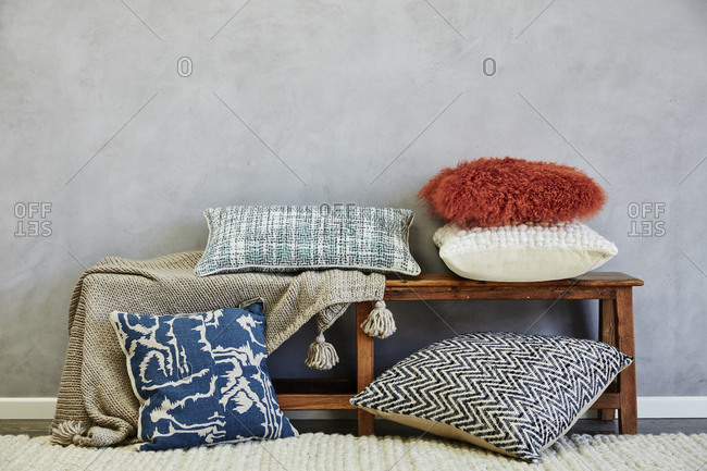 Pillows and blanket on a wooden bench
