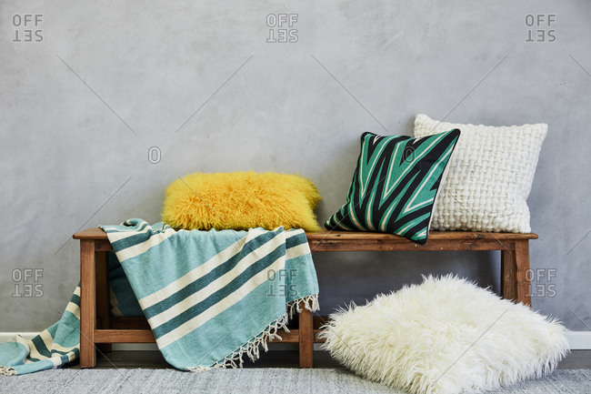 Colorful pillows and blanket on a wooden bench
