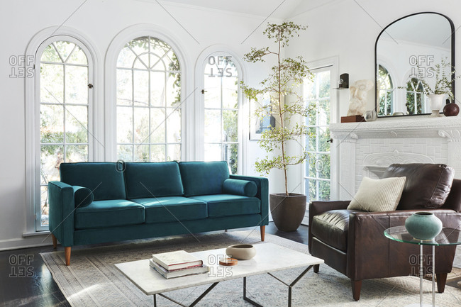 February 16, 2020: Interior shot of living room with tall arched windows and a velvet blue sofa