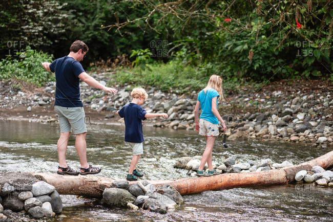 Father and two children crossing a river on a fallen tree