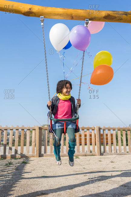Afro girl with curly hair swinging with five colored balloons tied to her wrist