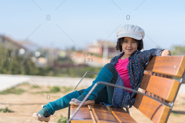 Happy little African-American girl with curly hair dressed in pink and blue with a white hat sitting on a bench
