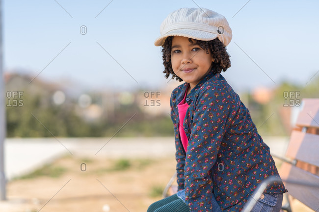 Little African-American girl with curly hair dressed in pink and blue with a white hat sitting on a bench